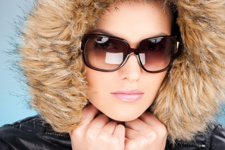 pretty woman wearing winter outfit with fur and glasses  photo