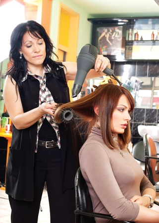 Pretty lady sitting while hairdresser dries her hair photo