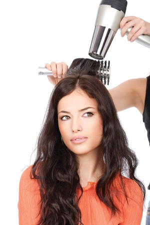 hairdresser is drain a woman's long black hair, isolated on white photo