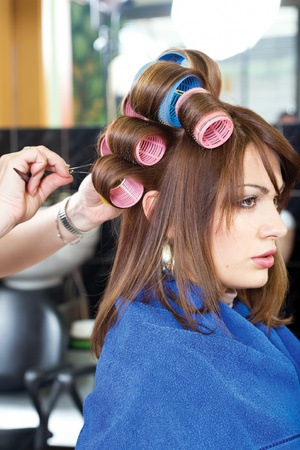 hairstylist pinching client's curlers Stock Photo - 12370162