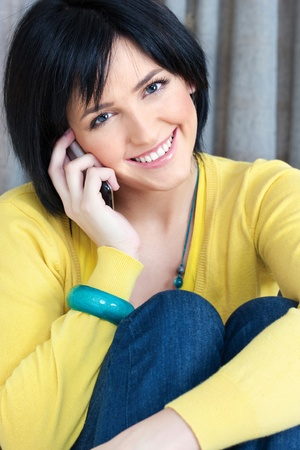 smiled: Pretty smiled girl using mobile phone at home Stock Photo