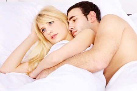Young couple in bed, he embracing her, focus on woman Stock Photo