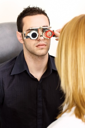 oculist: Male patient seeking medical attention at the optometrist, wearing trial frame for eye testing