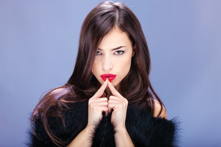 pelt: Portrait of a pretty woman with pelt holding fingers near lips Stock Photo