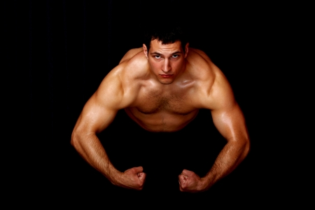 bodybuilder showing his strength, on black background photo