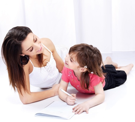 Woman and child drawing on notepad and laughing Stock Photo