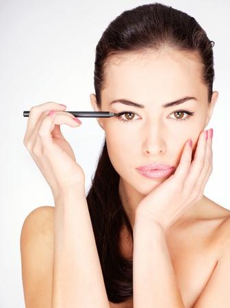 pretty woman applying cosmetic pencil on eye Stock Photo
