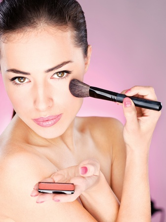 pretty woman applying cosmetic powder brush Stock Photo