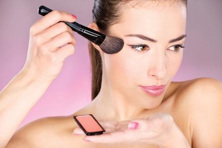 pretty woman applying cosmetic powder brush photo