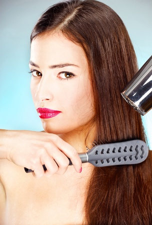 pretty woman with long hair holding blow dryer and comb photo