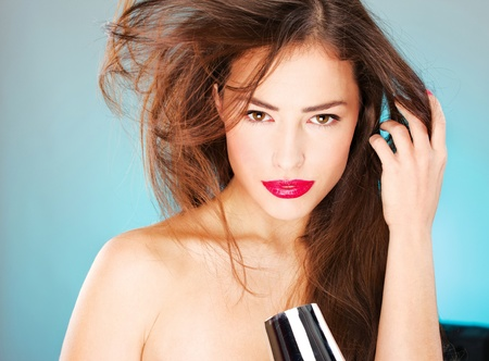 pretty woman with long hair holding blow dryer Stock Photo