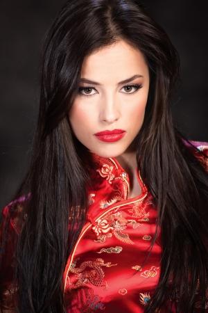 cheongsam: pretty woman in red Cheongsam on dark background