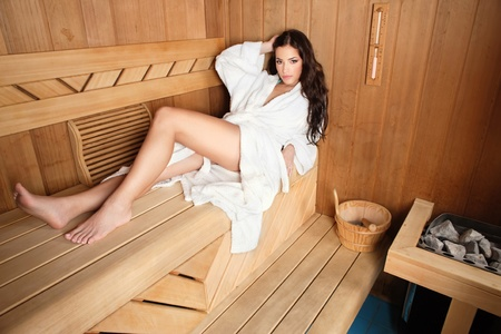 bathrobe: young woman relaxing in finnish type wooden sauna