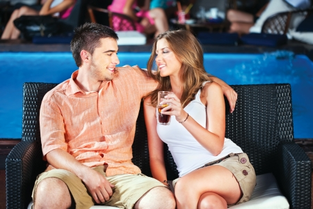 young couple outdoor near swimming pool on summer evening photo