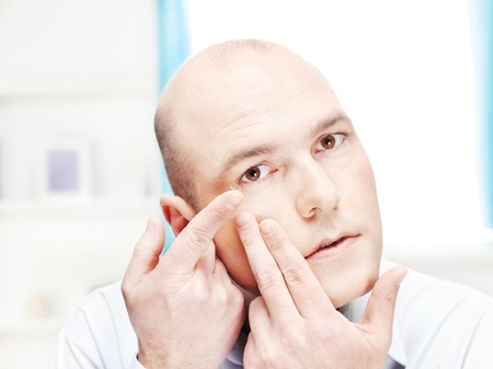 contact lens: Close up of a man putting contact lens in his eye at home Stock Photo
