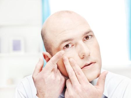 lentes de contacto: Primer plano de un hombre que pone la lente de contacto en el ojo en el hogar