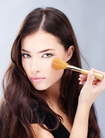 makeup a brush: Portrait of a pretty young woman holding powder brush