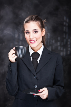 Pretty young woman holding black cup of coffee photo
