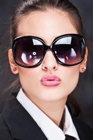 mujer con corbata: Chica guapa con gafas de sol grandes que env�an beso