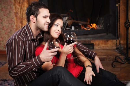 Happy couple in love enjoying wine near fireplace