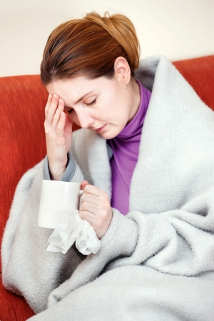A young sick woman with a cup of tea in her hand. She hold her head in pain
