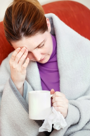 A young sick woman having headache, holding cup of tea and handkerchief photo