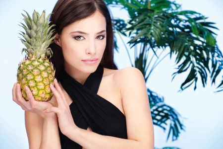 Pretty woman holding pineapple in front of a palm tree photo