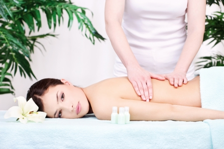 Pretty woman on back massage in spa center Stock Photo