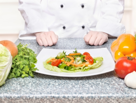 Salad on plate in front of a chef photo