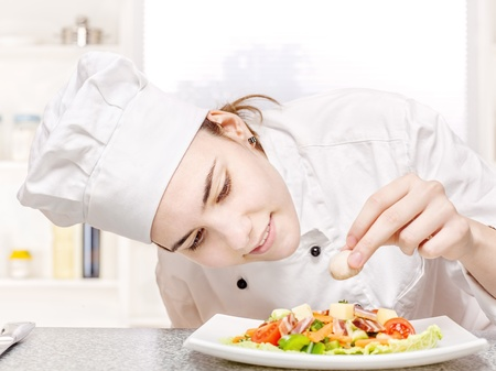 pretty young chef decorating delicious salad