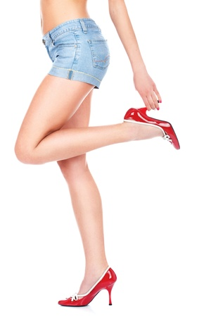girl in denim skirt with sexy legs standing, isolated on white background Stock Photo