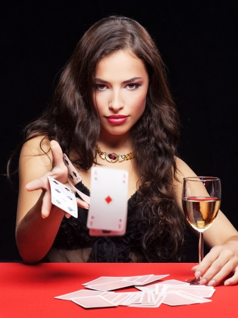 casinos: pretty young woman gambling on red table