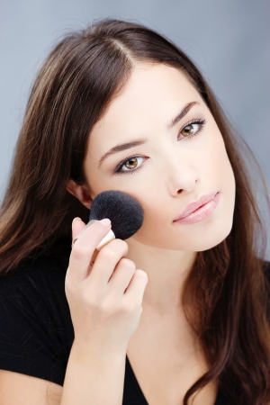 woman doing makeup with powder brush