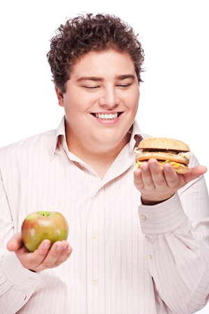 Young chubby man holding apple and hamburger, isolated on white photo