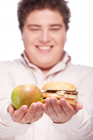 apple and hamburger in hands of a young chubby man, isolated on white photo