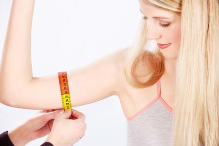 Measure tape around womans arm
