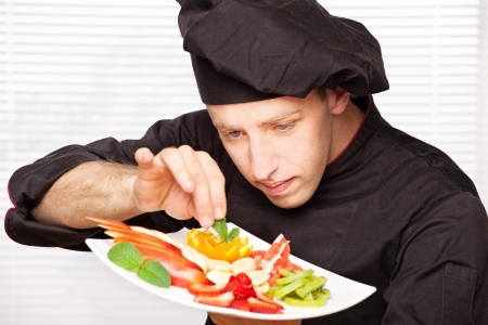 chef in black uniform decorating delicious fruit plate