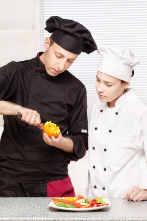 Senior chef teaches young chef to decorate fruit plate in kitchen photo