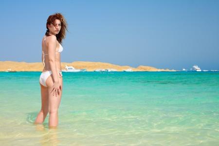 sensational: pretty woman wearing white bikini on a paradise beach