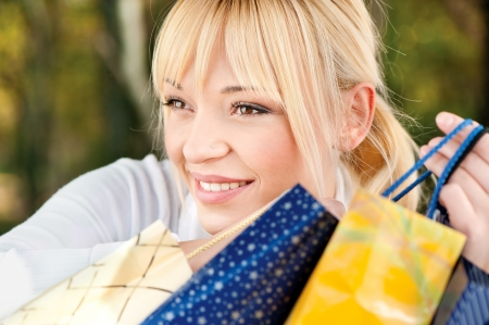 Beautiful young blond with shopping bags, outdoor photo
