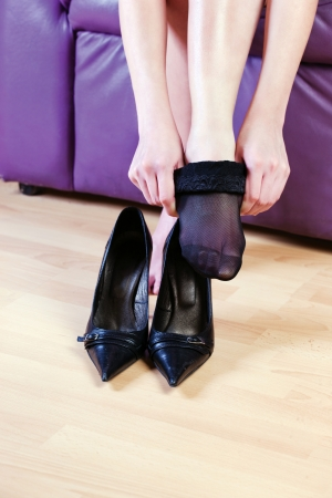 woman dressing black nylon sock
