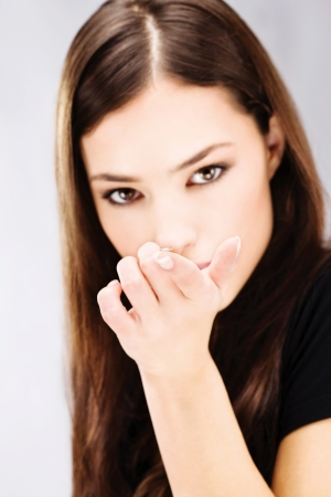 Young woman holding contact lens on finger in front of her face photo
