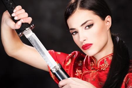 Pretty woman holding katana weapon photo