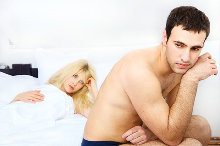 relationship of a unhappy young couple in bedroom, focus on male