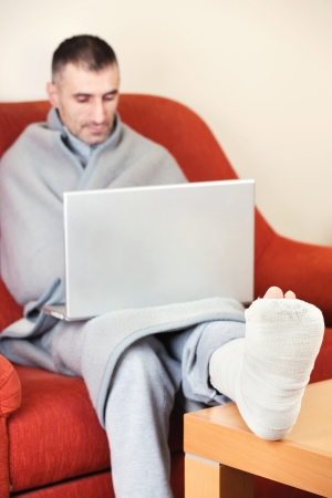 crutch: man with a broken leg on a sofa at home  working on laptop