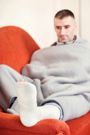 plaster foot: man with a broken leg on a sofa at home