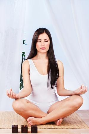 Pretty woman in lotus pose at meditation photo
