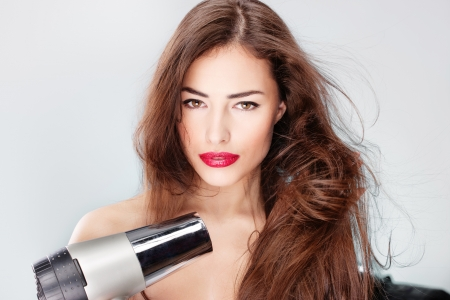woman with long hair holding blow dryer photo