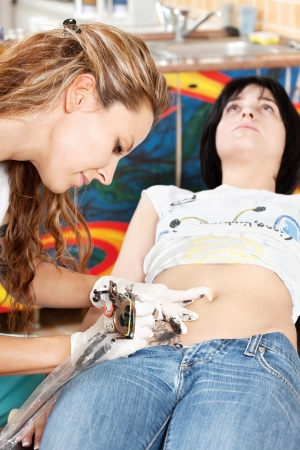 woman wearing gloves and making a tattoo on customers belly photo