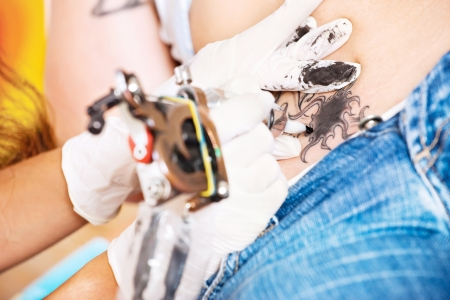 tattooing: hands of a tattoo artisan making art on belly Stock Photo